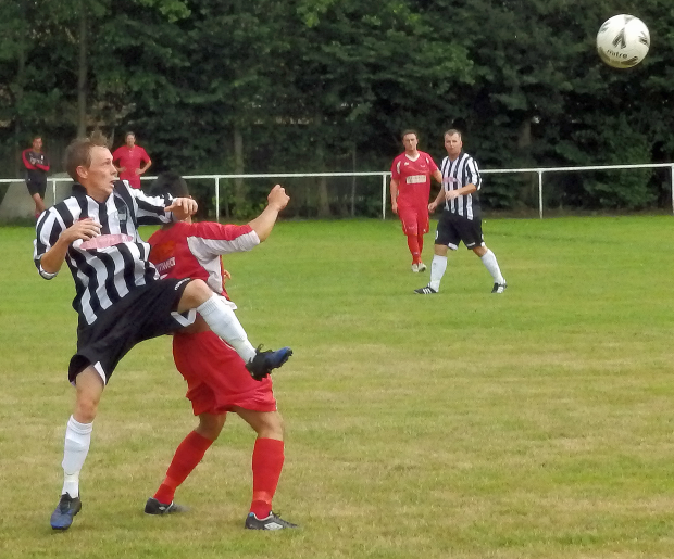 A Penydarren defender challenges a Ton Pentre player for the ball.