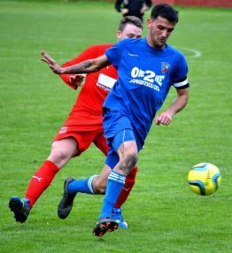 Yeates defends well for Fairfield United under pressure from Jaymie Wearn.