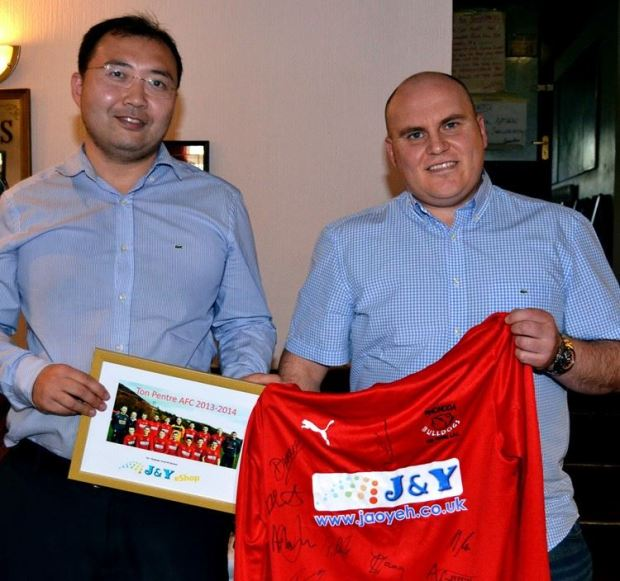 Ceri Jones (right), Ton Pentre's Commercial Manager, presents Mr Yu Li with a signed shirt to thank him for his home kit sponsorship.